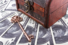 Keep money safe. US dollars background wtih part of a wood treasure chest and old skeleton key stock photography