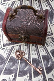 Money savings. US dollars background wtih a wood treasure chest and old skeleton key Stock Image