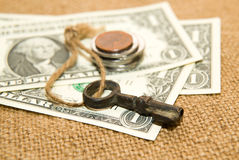 US dollars banknotes, coins and key on an old cloth Royalty Free Stock Image