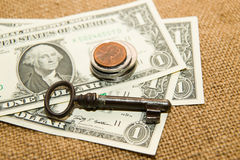 US dollars banknotes, coins and key on an old cloth Stock Image