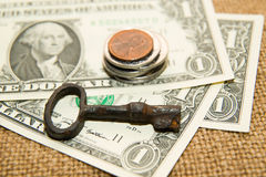US dollars banknotes, coins and key on an old cloth Royalty Free Stock Photos