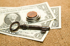 US dollars banknotes, coins and key on an old cloth Stock Photography