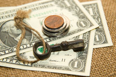 US dollars banknotes, coins and key on an old cloth Royalty Free Stock Photography