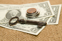 US dollars banknotes, coins and key on an old cloth Royalty Free Stock Photo