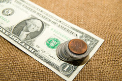 US dollars banknotes and coins on an old cloth Stock Image