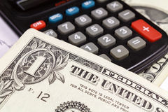 US dollars banknotes lying on the surface of the electronic calculator. Focus in the banknote Royalty Free Stock Photo