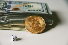 Us dollars, bitcoin and rolling dice. New era - crypto currency is here, in full blooming, bitcoin against pile of 100 dollar bills and rolling dice as a symbol Stock Photo