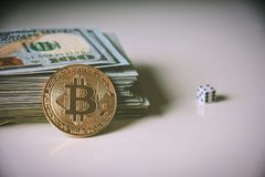Us dollars, bitcoin and rolling dice. New era - crypto currency is here, in full blooming, bitcoin against pile of 100 dollar bills and rolling dice as a symbol Stock Image