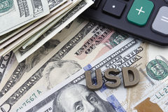 US Dollars and a calculator. US Dollar banknotes, a calculator, and metal letters saying USD Stock Photography