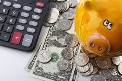 US Dollars With a Calculator And a Piggy Bank. US Dollar coins and notes, together with a piggy bank and a calculator Royalty Free Stock Photos