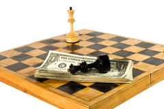 US dollars and chess figures on a chessboard. US dollars and chess figures on an old wooden chessboard Stock Photography
