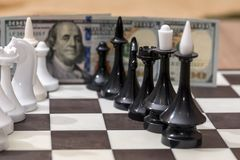 US dollars and chess figures. On chessboard Stock Photos