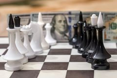 US dollars and chess figures. On chessboard Stock Image