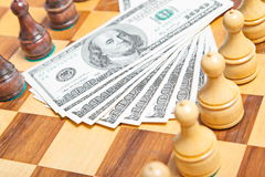 US dollars and chess figures on an old chessboar. US dollars and chess figures on an old wooden chessboar Royalty Free Stock Photos