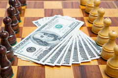 US dollars and chess figures on an old chessboar. US dollars and chess figures on an old wooden chessboar Stock Photo
