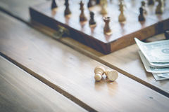 US dollars and chess figures on an old wooden Stock Photos
