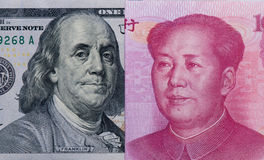 US dollars and Chinese Yuan bill. Macro close up shot of  U.S. dollars bills Franklin and renminbi Chinese Mao zedong portrait Royalty Free Stock Photography