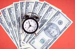 US dollars with clock on red background composition. Flat lay and top view photo money business finance currency concept financial cash investment bank economy royalty free stock photos