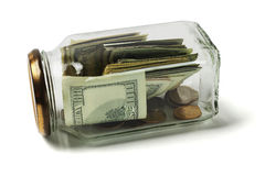 US Dollars and Coins in Glass Jar Stock Images