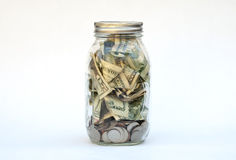 US dollars and coins in a glass jar Royalty Free Stock Images