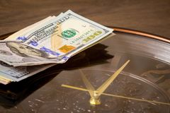 US dollars lie on the big clock. Time to earn money. Time is money_. US dollars lie on the big clock. Time to earn money. Time is money stock photo