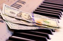 US-Dollars liegen auf den Klavierschlüsseln Zahlung für das Konzert, Gewinn von der Ausführung des musikalischen works_ stockfotografie