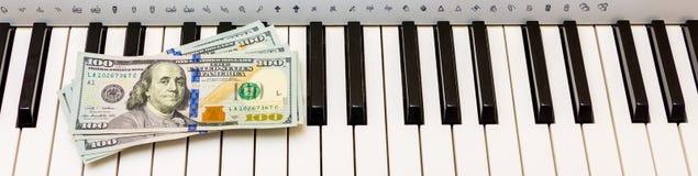 US-Dollars liegen auf den Klavierschlüsseln Zahlung für das Konzert, Gewinn von der Ausführung des musikalischen works_ lizenzfreies stockfoto