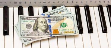 US-Dollars liegen auf den Klavierschlüsseln Zahlung für das Konzert, Gewinn von der Ausführung des musikalischen works_ stockbilder