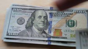 US 100 Dollarscheine schnell ausbreitend und auf einer Tabelle gezählt stock video footage