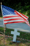 US Flag. A small United States flag over a grave with a cross in the background Royalty Free Stock Photography