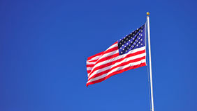 US Flag. A US Flag flying on top of a flag pole.  The wind straightens it out for visiblity Stock Photography