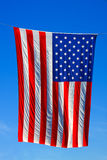 US Flag. United States of America flag with blue sky background Royalty Free Stock Photo