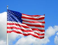 US Flag. Against a vibrant blue sky, a United States Flag blows in the wind Stock Photos