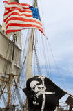 US and Black Flag on Sailer. Sailing ship with flag of the USA and a Jolly Roger Royalty Free Stock Photography