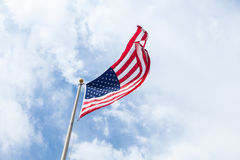 US flag on blue sky with clouds Royalty Free Stock Images