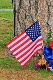 Us Flag Closeup. A US Flag shot closeup on Memorial Day with a tree trunk in the back ground with flower's and grass that's bright and colorful. Shot in Kansas Stock Photos