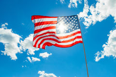 US flag with cumulus clouds and blue sky on background Stock Images
