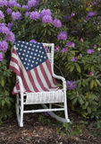 US Flag draped on a antique white wicker chair. A large US flag draped on a antique white wicker chair-concept Stock Photo