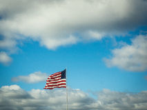 US Flag Flying in Blue, Cloudy Sky Stock Image