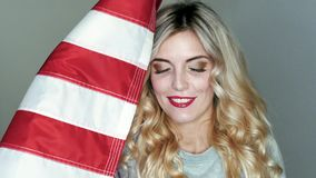 The US flag is in the hands of a brilliant blonde. Posing in studio stock video