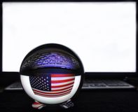 US flag and keyboard in reflection on a crystal ball against a white monitor stock photo