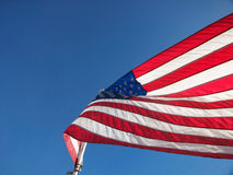 US Flag. Large, flapping US flag in beautiful sun with red, white and blues stripes and gold stars Royalty Free Stock Images