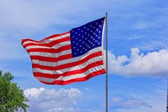 US FLAG MEMORIAL DAY. A US Flag with a tree with  blue sky and white cloud's on Memorial day that's bright and colorful Stock Photography