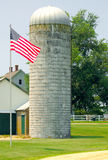 US flag near farm silo. A view of the United States flag on a lawn near a farm silo in rural Maryland royalty free stock photo