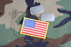 US flag patch with dog tags on woodland camouflage uniform. Background Stock Photos