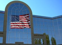 US Flag Reflection. The reflection of a US flag from the windows of an office building Stock Image