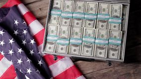 US flag, suitacse and money. Man opens case with dollars. Land of opportunity welcomes you. Resources of the government stock footage