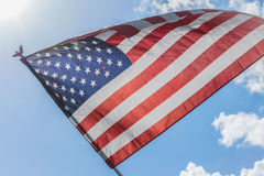 US flag waving in bright sunlight and blue sky. Low angle view looking up at American flag blowing outside on sunny day with clouds royalty free stock photos