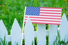 The US flag on a white fence against the background of blooming green grass stock photo