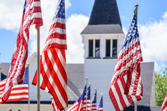 US flags waving in front of white church. Multiple American flags waving with church steeple in background on sunny day stock images